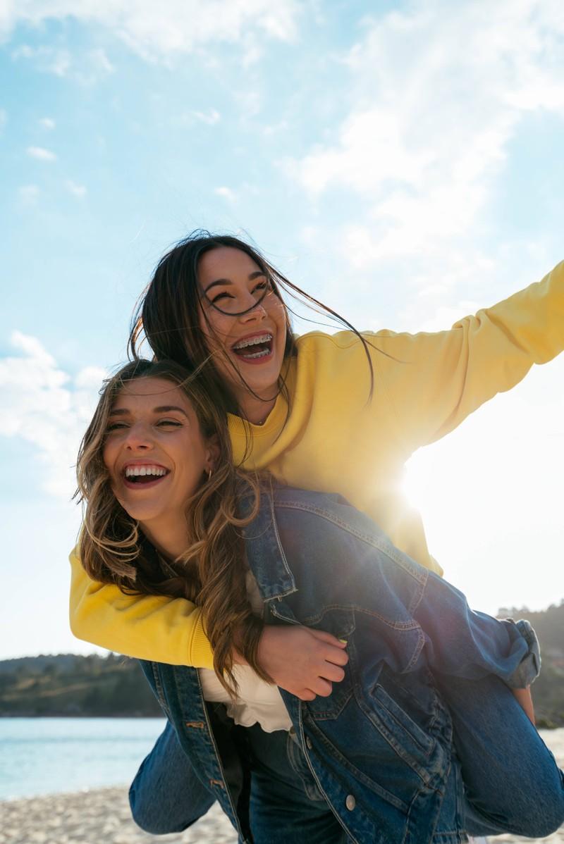 Eine junge Frau trägt eine andere junge Frau Huckepack an einem Strand.