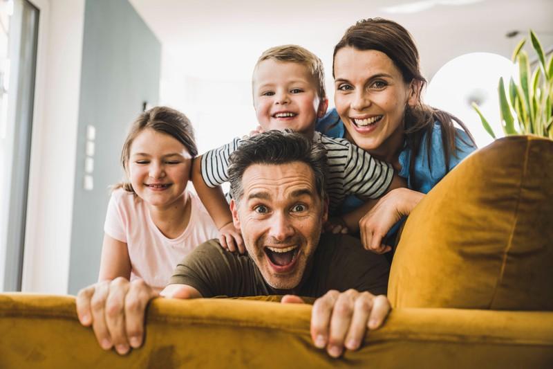 Eine vierköpfige Familie sitzt auf auf dem Sofa und lacht in die Kamera.