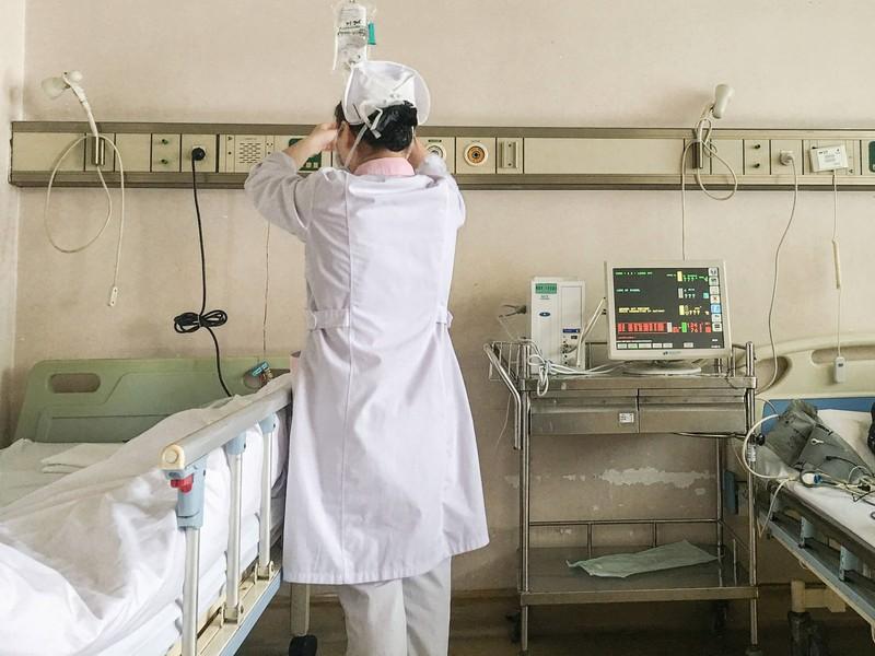 Eine Krankenschwester reguliert Medikamente an einem Patientenbett im Krankenhaus.