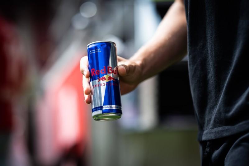 Zu sehen ist die Nahaufnahme eines Mannes, der eine Red Bull-Dose in der Hand hält.