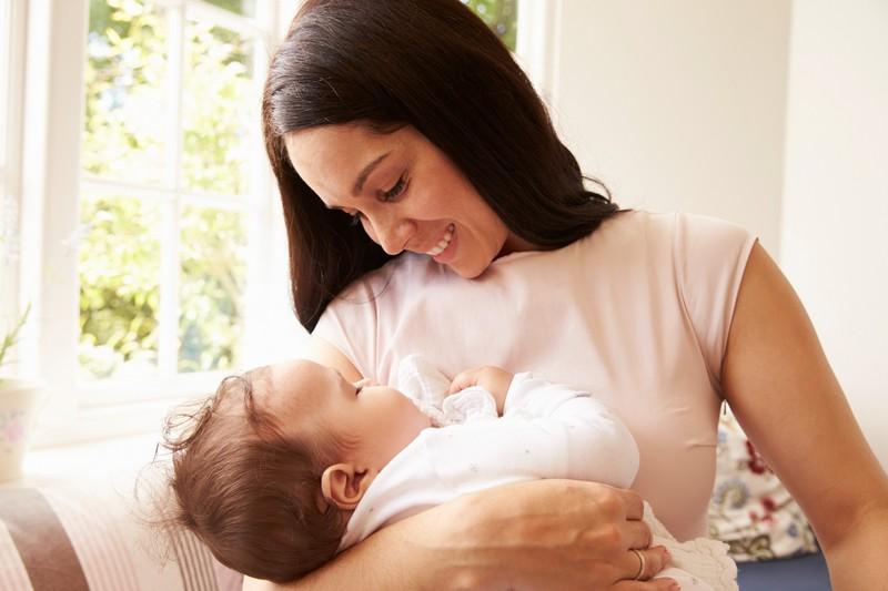 Eine Mutter hält ihr Baby auf dem Arm und lächelt es an.