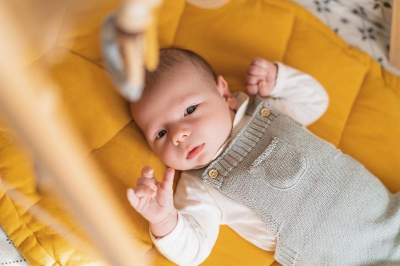 Zu sehen ist ein Baby, das in der Krippe liegt und in die Kamera schaut.
