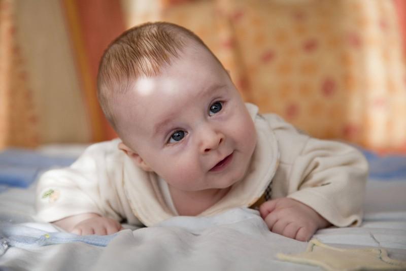 Zu sehen ist ein Baby, das auf dem Bauch liegt.