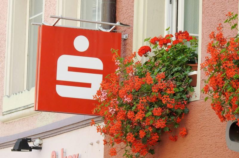 Zu sehen ist das Logo der Sparkasse an einer Häuserwand.