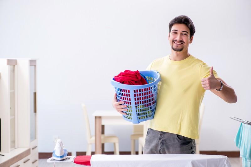 Ein Mann hält einen Wäschekorb in der Hand und schaut in die Kamera.