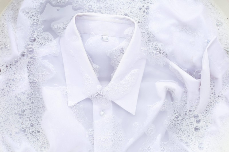 Zu sehen ist ein weißes Hemd, das in Wasser gewaschen wird.