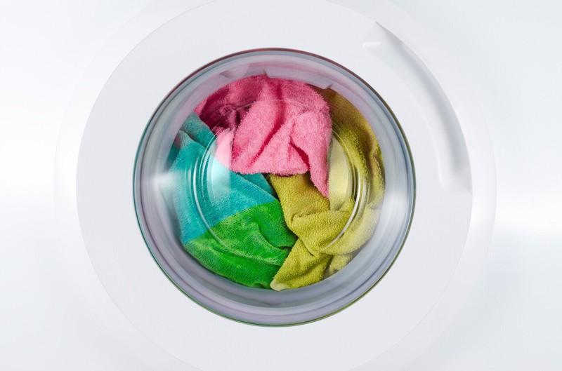 Zu sehen ist eine Waschmaschine, die mit bunter Kleidung gefüllt ist.