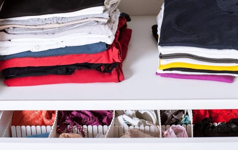Zu sehen sind zusammengelegte Kleidungsstücke in einem Kleiderschrank.