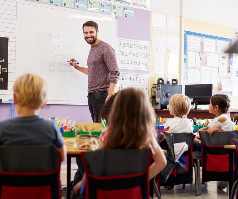 Ein junger attraktiver Lehrer vor seiner Klasse.