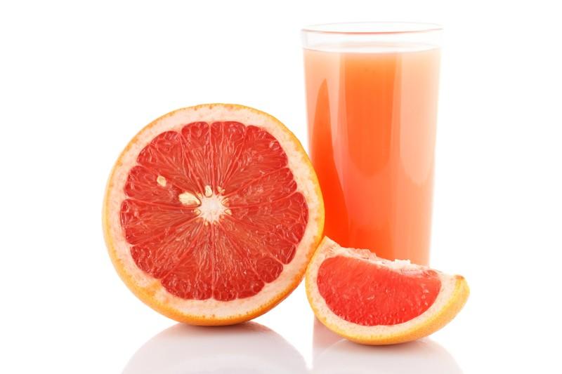Grapefruits neben einem Glas Saft