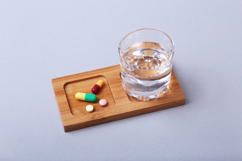 Medikamente neben einem Glas Wasser
