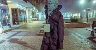 Menschen hängen Jacken an Bäume für Obdachlose
