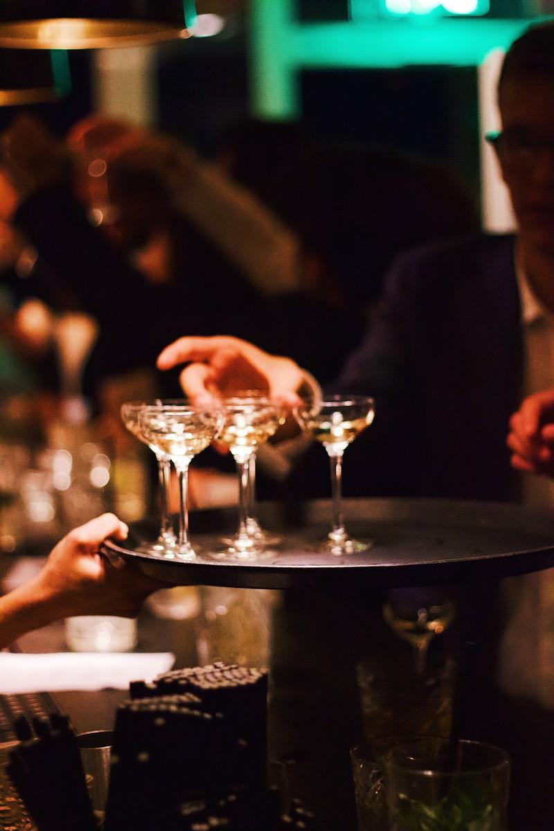 Ein Kellner bringt Cocktails, die die Geschichte des Onkels und das Familiendinner noch aufheitern werden
