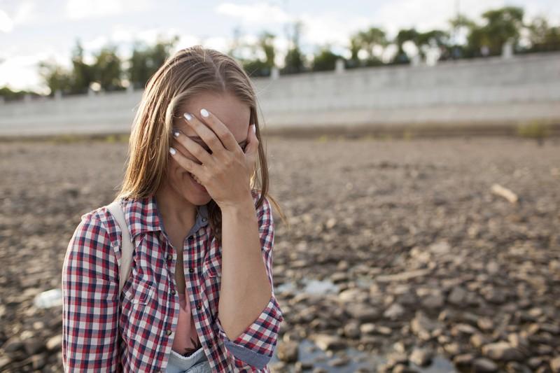 Peinlich: Eine Frau bedeckt ihr Gesicht vor Scham