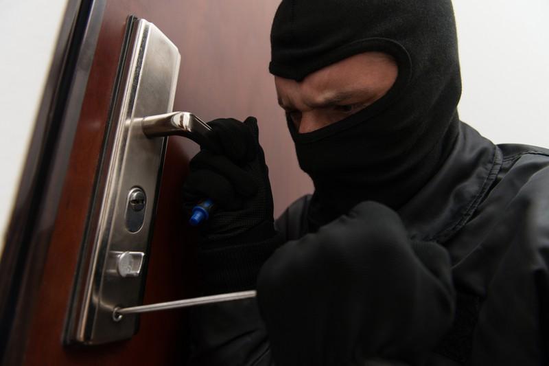 Ein Einbrecher öffnet eine Tür