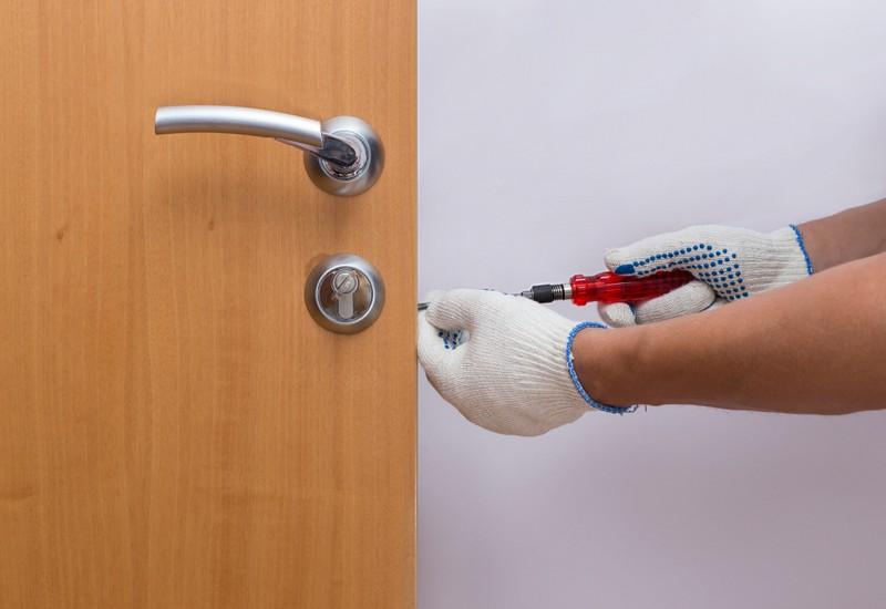 Ein Mann bringt ein neues Türschloss an