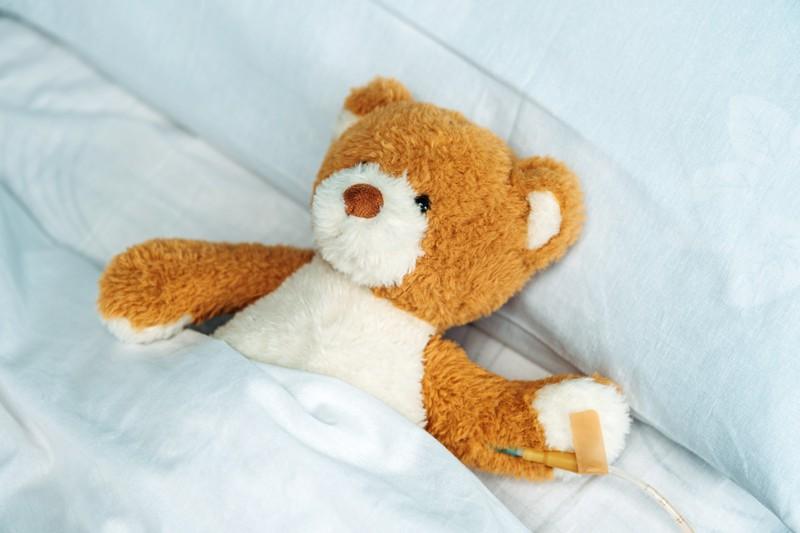 Ein Teddybär liegt im Bett