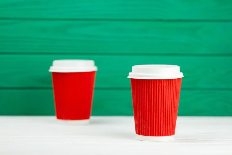 Zwei rote Pappbecher vor einer grünen Wand
