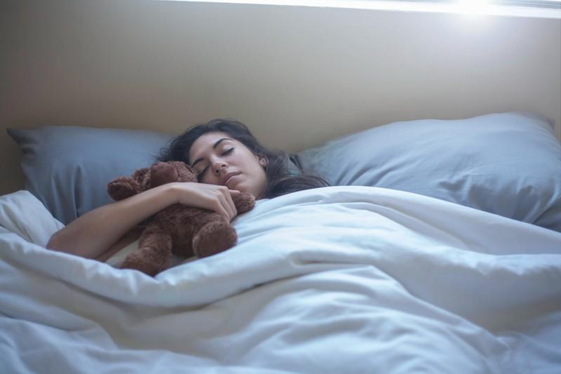 Schlafende Frau im Bett mit Teddybär