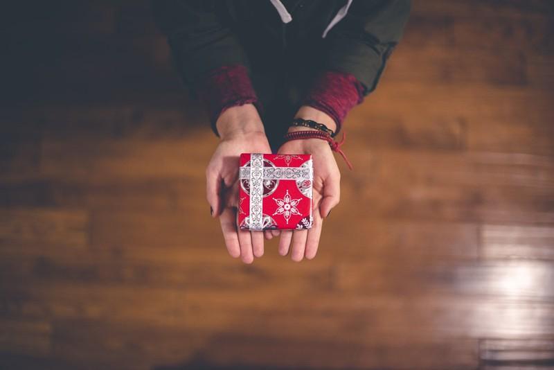 Auf diesem Bild sieht man ein Kind, das an Weihnachten ein Geschenk in der Hand hält.