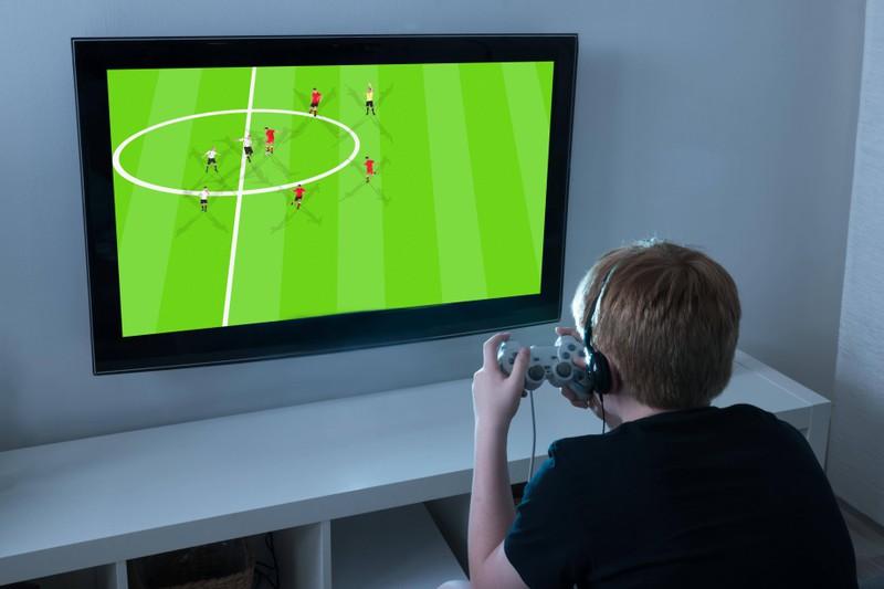 Auf diesem Bild sieht man ein Kind, das vor einem Fernseher steht.