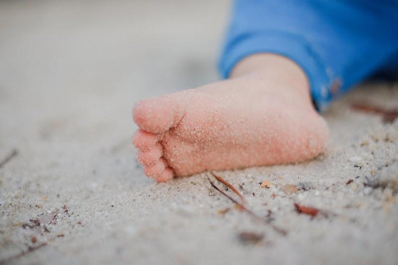 Dieses Bild zeigt ein kleines Kind, das im Sand mit Steinen und Stöcken spielt.