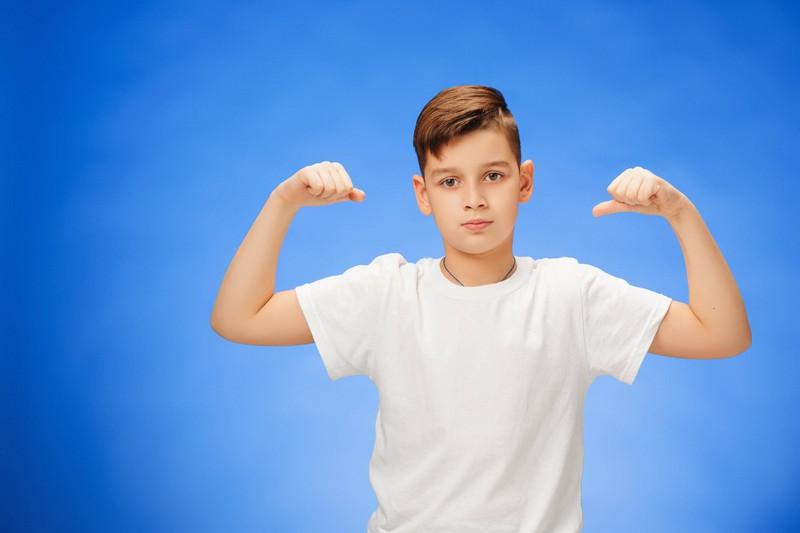 Dieses Bild zeigt einen kleinen Jungen, der Wrestler oder Superheld sein möchte und von Muskeln träumt.