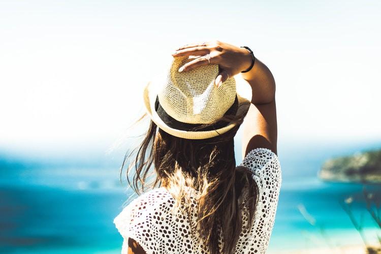 Man sieht eine Frau in der Sonne und es geht um den Tipp richtige Kleidung bei Hitze.