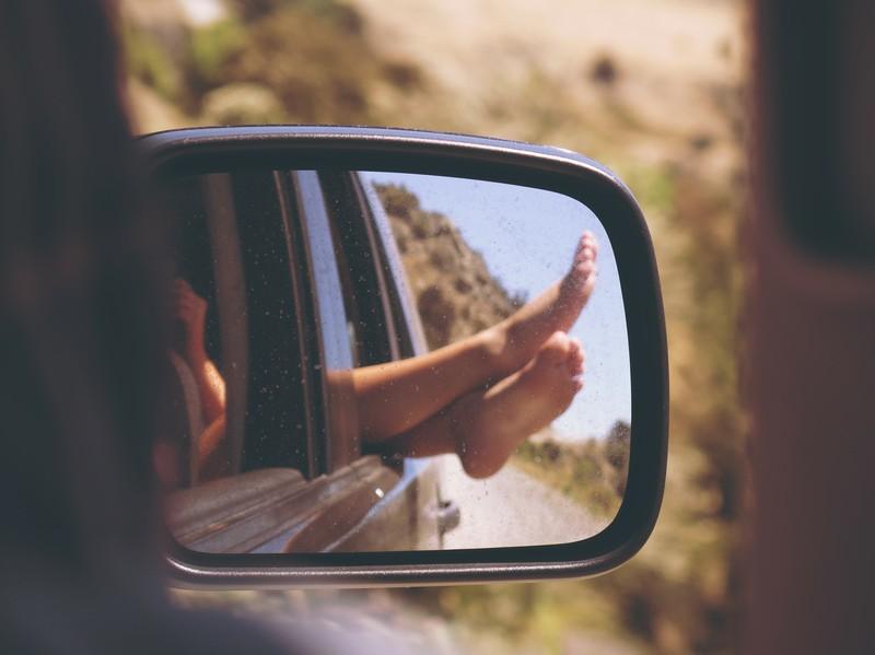 Man sieht eine Frau im Auto und es geht um den Tipp, Pausen bei Autofahrten zu machen bei Hitze.