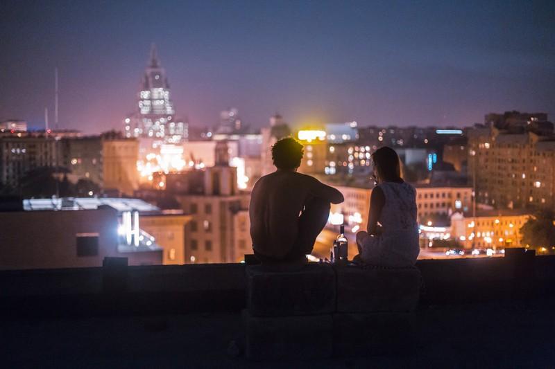 Paar, das bei Nacht draußen sitzt und sich unbeobachtet fühlt