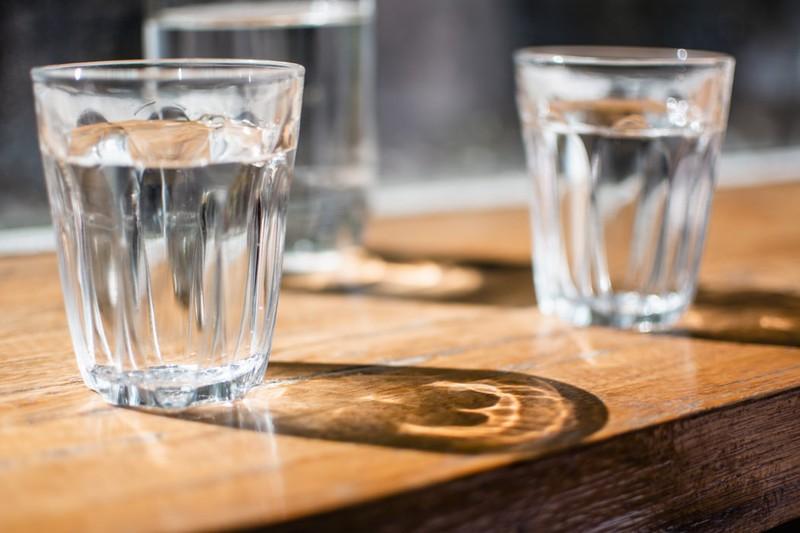 Zwei Gläser Wasser, die nebeneinander auf dem Tisch stehen