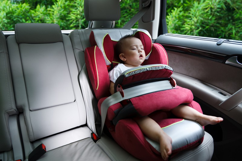Kleiner Junge schläft im Auto