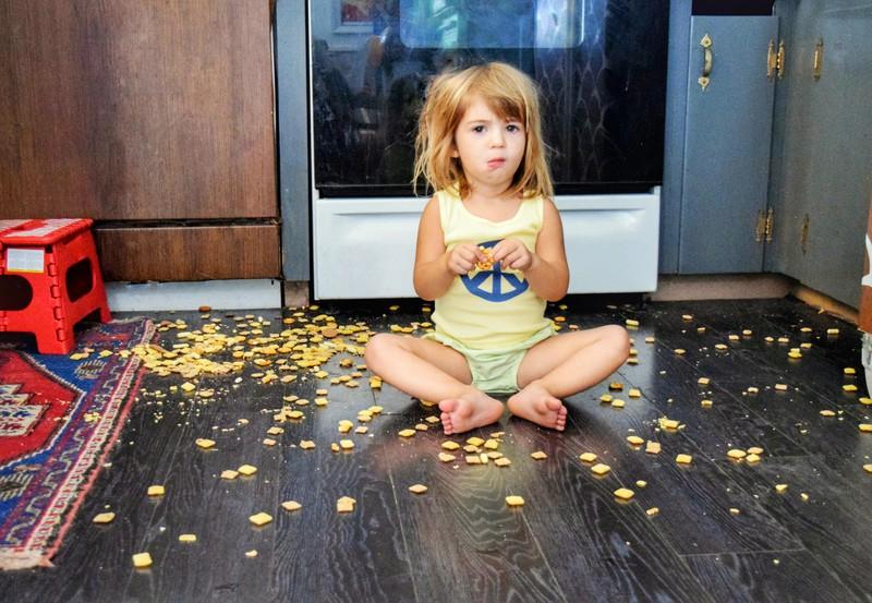 Kleinkind sitzt zwischen Cornflakes auf dem Boden