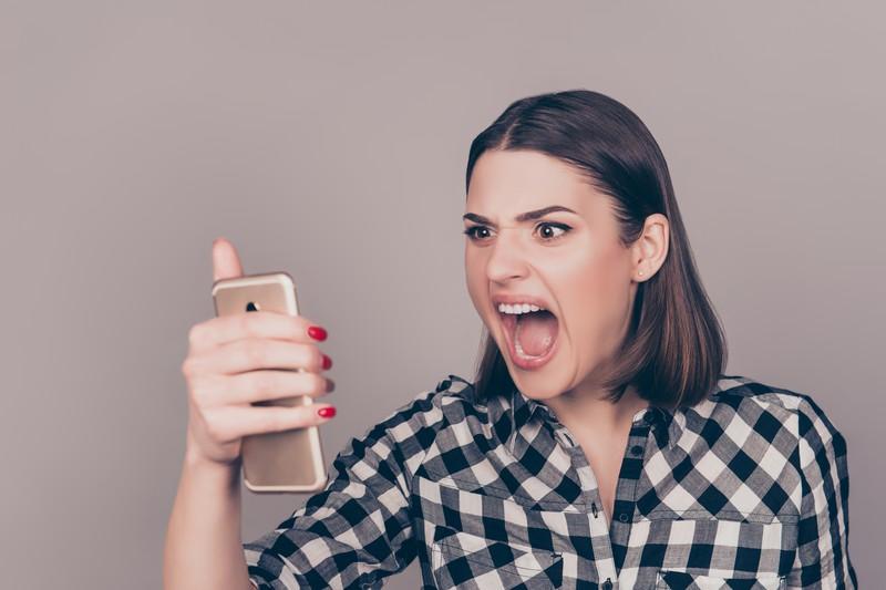 Frau schreit Telefon an