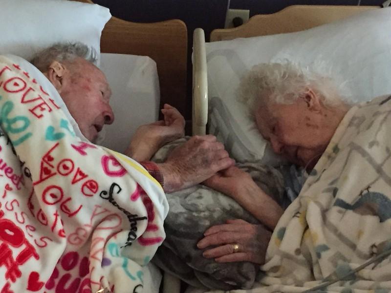 Zwei ältere Menschen halten sich kurz vor ihrem Tod an den Händen