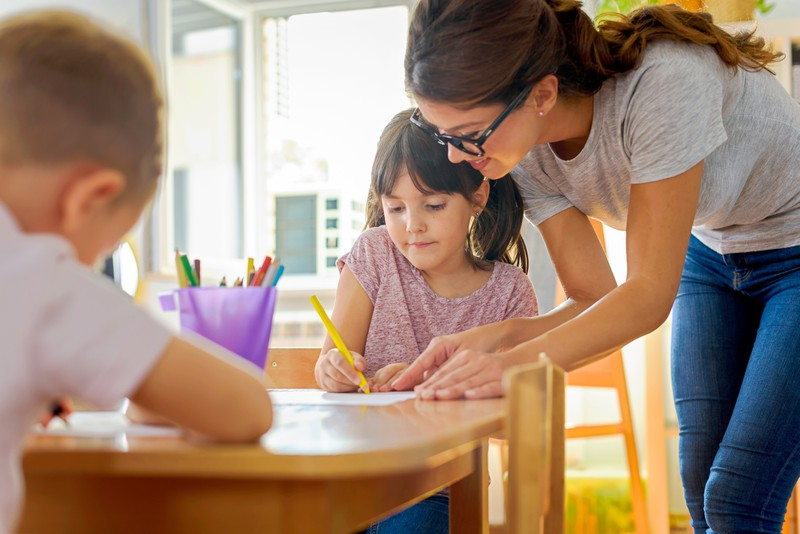 Kinder zeichnen mit Vorschullehrerin