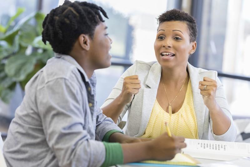 Lehrerin diskutiert mit Schüler