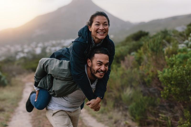 Mann trägt Frau auf dem Rücken