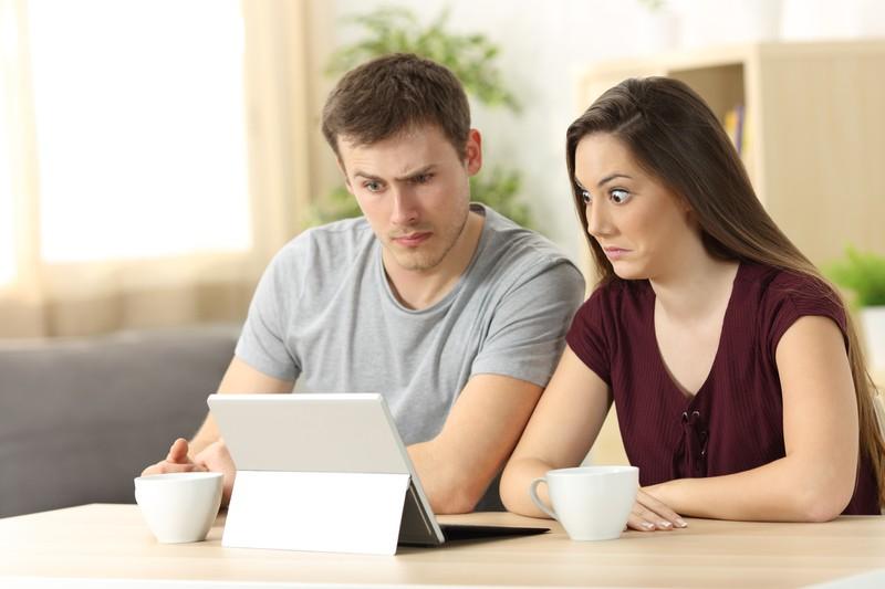 Paar schaut geschockt auf Laptop