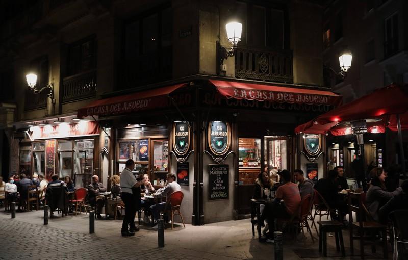 Man sieht den Außenbereich eines Restaurants oder einer Bar, auf der viele Kunden sitzen