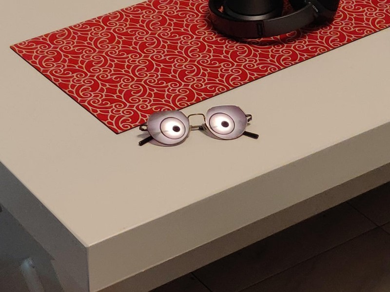 Brille auf dem Tisch, die uns eine optische Täuschung vorspielt. Es ist aber nur eine Reflektion