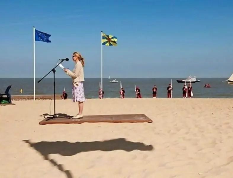 Das Bild zeigt eine Frau die eine Ansprache hält und schwebt. Es ist aber nur eine Täuschung