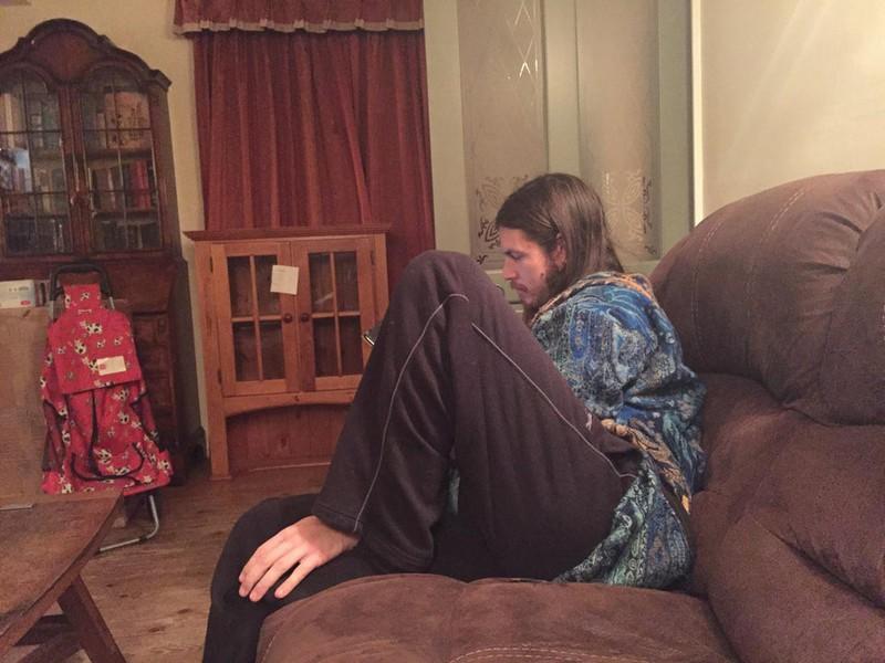 Mann auf Sofa, aber irgendwas stimmt nicht. Sein Fuß sieht aus wie eine Hand