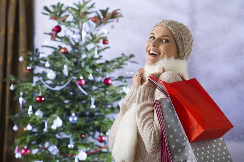 Man erkennt eine Frau vor dem Weihnachtsbaum mit Shoppingtüten voller Weihnachtsgeschenke