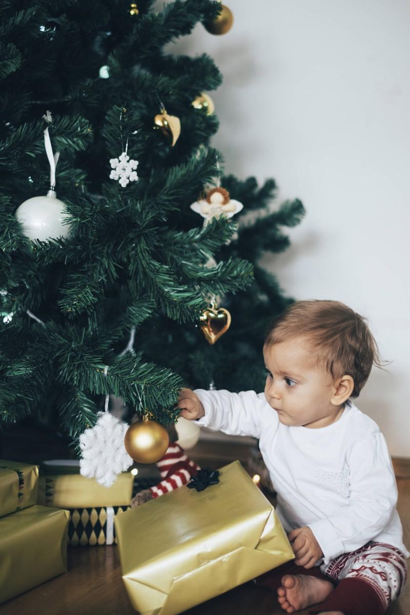 Man sieht ein Kleinkind mit einem Weihnachtsgeschenk, vermutlich ein Spielzeug