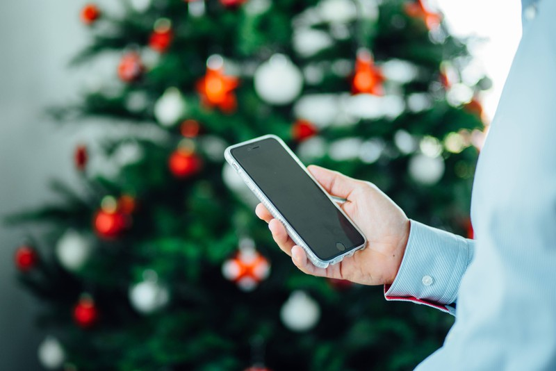 Man sieht ein Smartphone vor einem Weihnachtsbaum, das Elektrogerät ist das Weihnachtsgeschenk