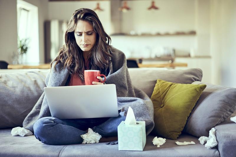 Eine Frau, die offensichtlich an einer Erkältung leidet und auf ihrem Sofa sitzt