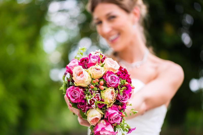 Eine Frau hält ihren Brautstrauß in die Kamera