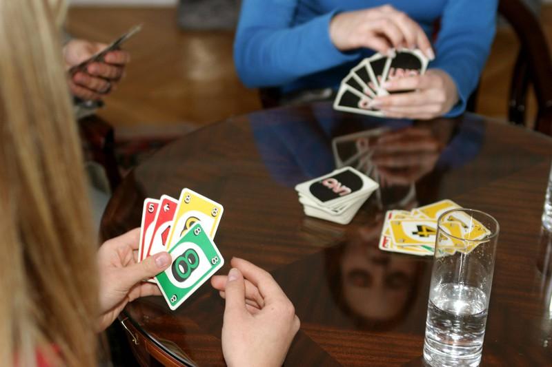 Menschen spielen UNO Karten, aber die Macher lösen eine Regel auf.