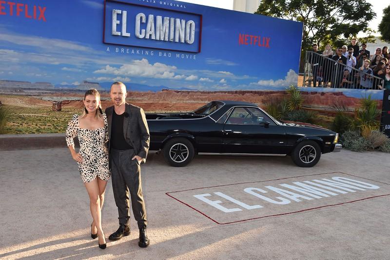 Aaron Paul steht vor Leinwand zu seinem neuen Film El Camino der auf Netflix läuft, Aaron Paul äußerte sich kritisch gegenüber der neuen Möglichkeit, Filme auf Netflix schneller abspielen zu können